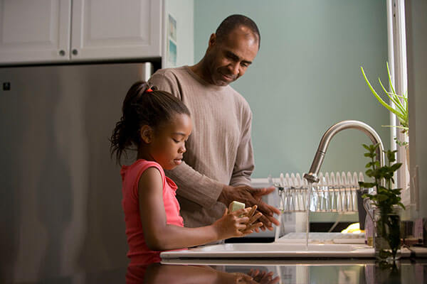 Father and daughter at sink